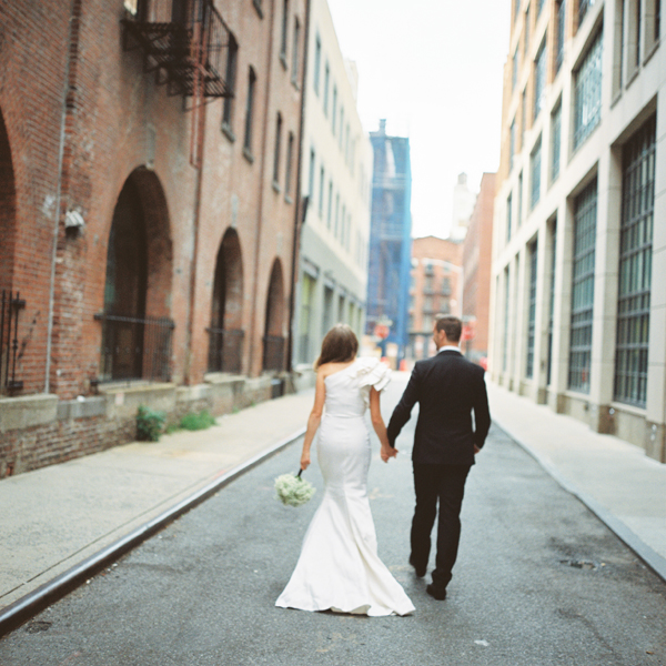 Couple holding hands walking down a city street.