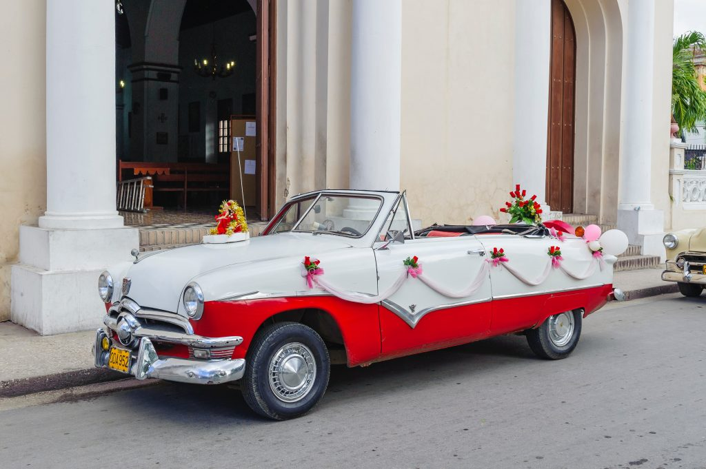 Old-fashioned car decorated with flowers and ribbon parked in front of a building.