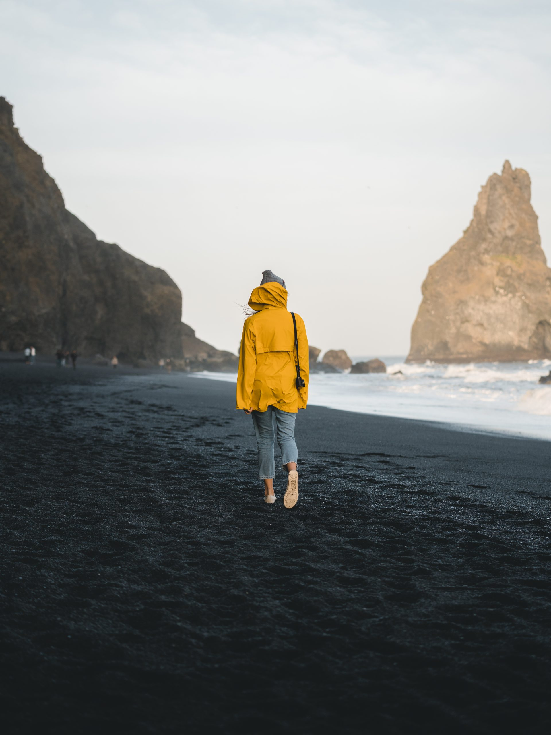 A woman in a yellow raincoat walking on a black sand beach