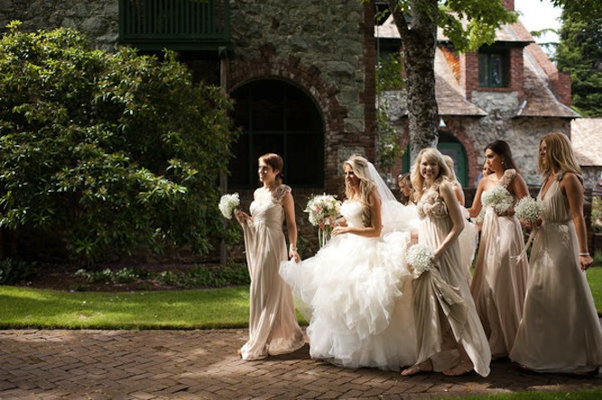 Bridesmaids holding bride's wedding dress.