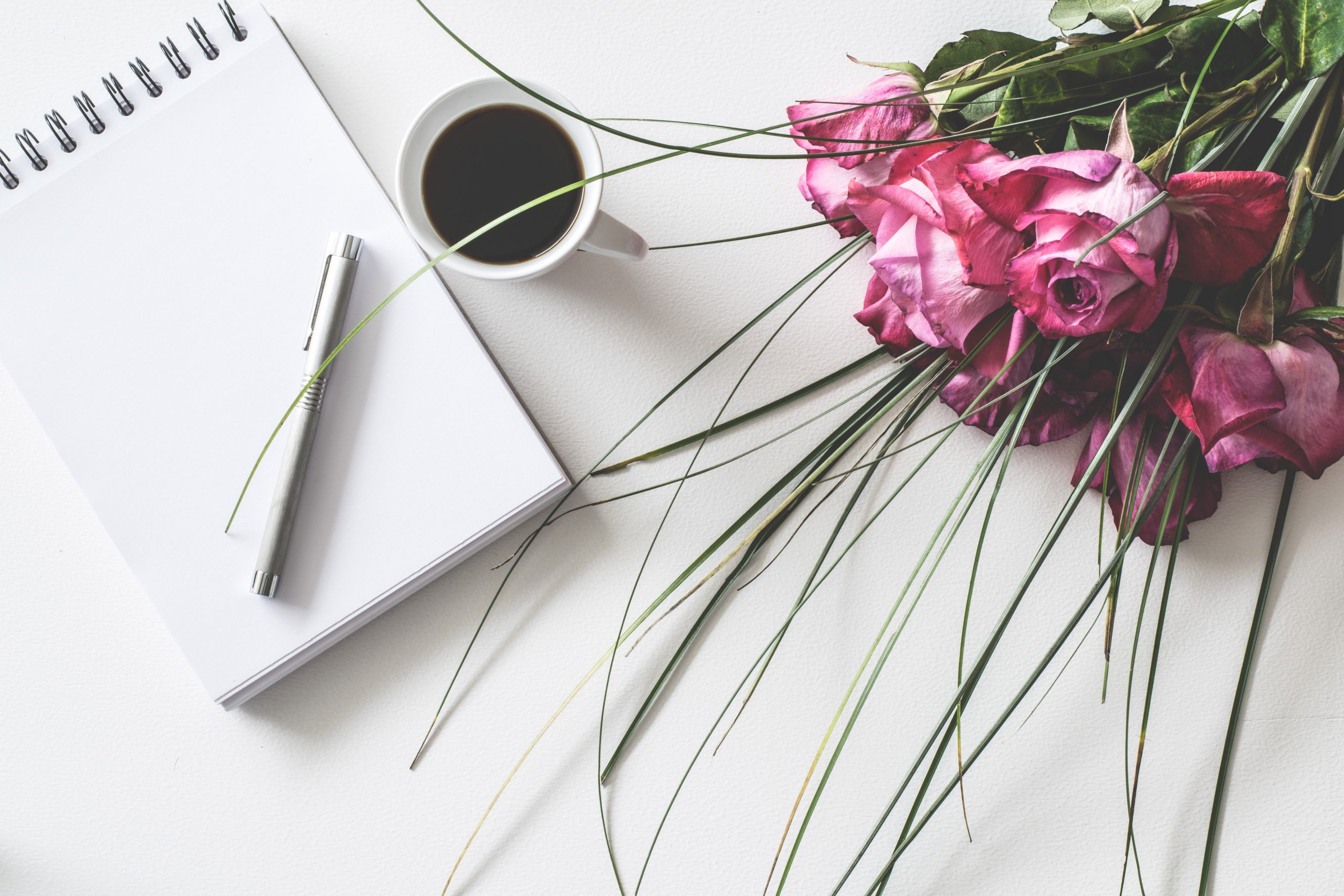 Open notepad with cup of coffee and bouquet of flowers on white surface.
