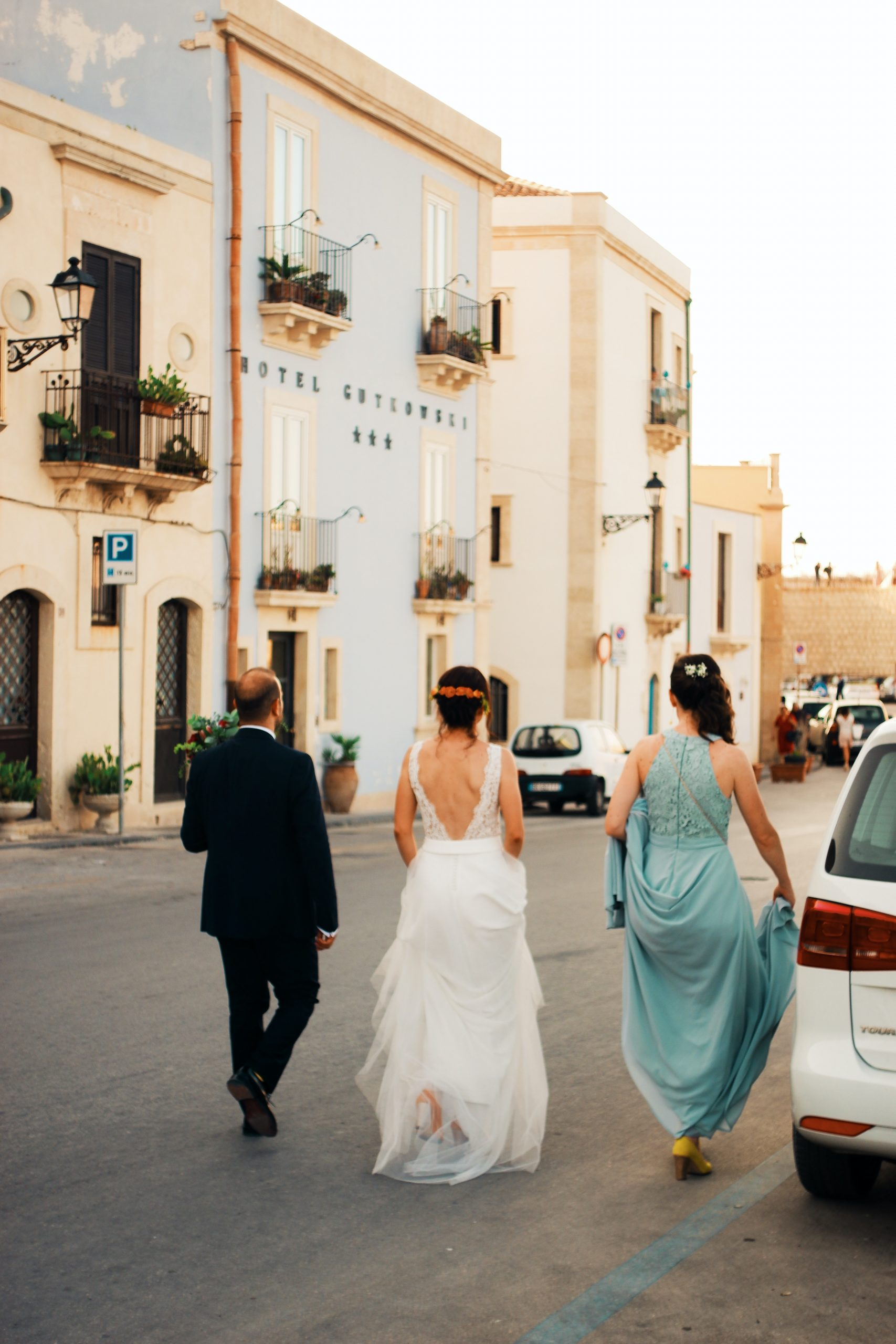 Bride with father and maid of honor walking down street.