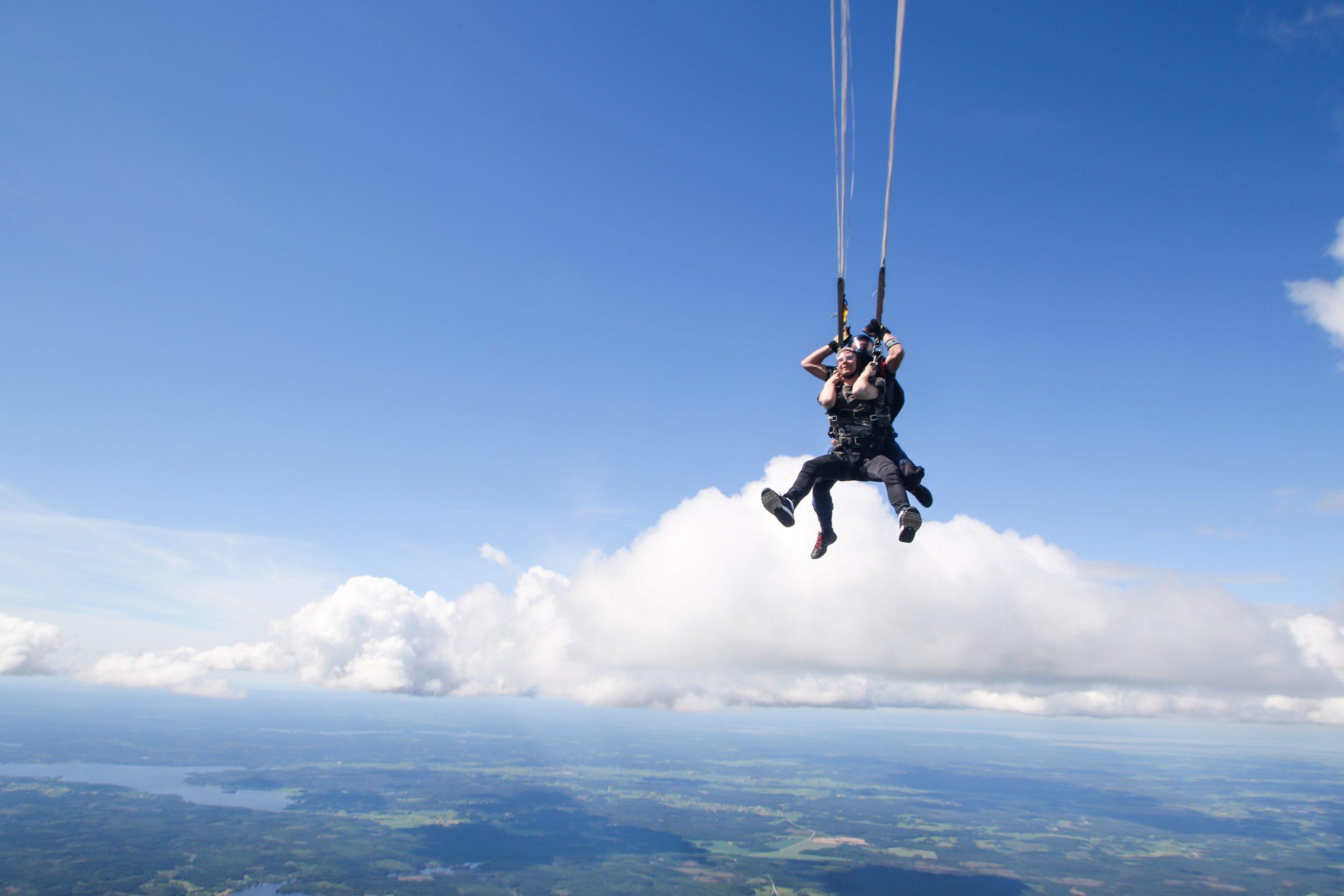 couple parachuting over skyline