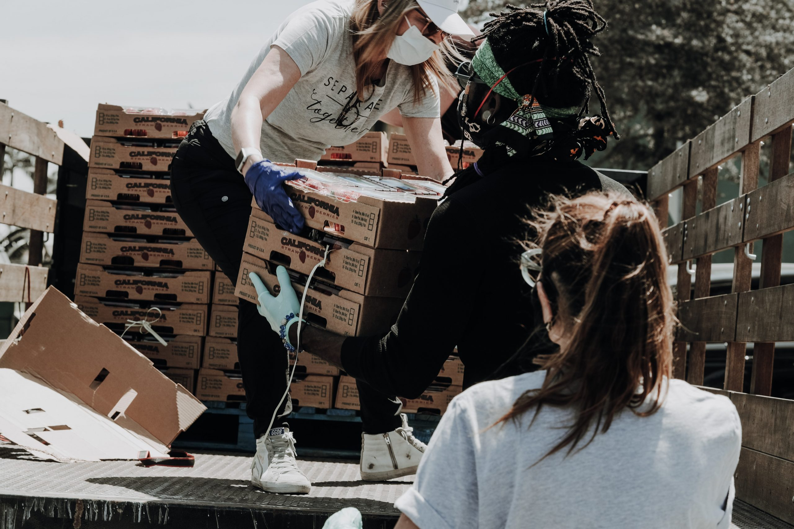 people helping unload boxes from truck for charity