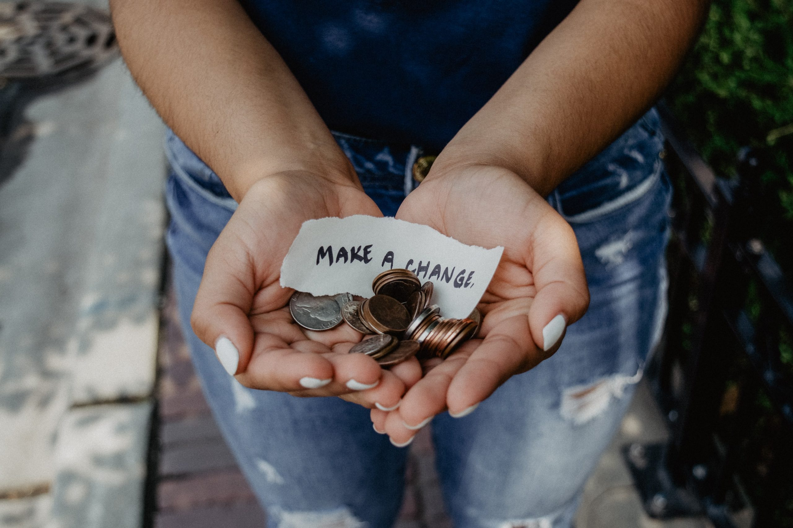 """person holding coins in their hands with note that reads """"make a change"""""""