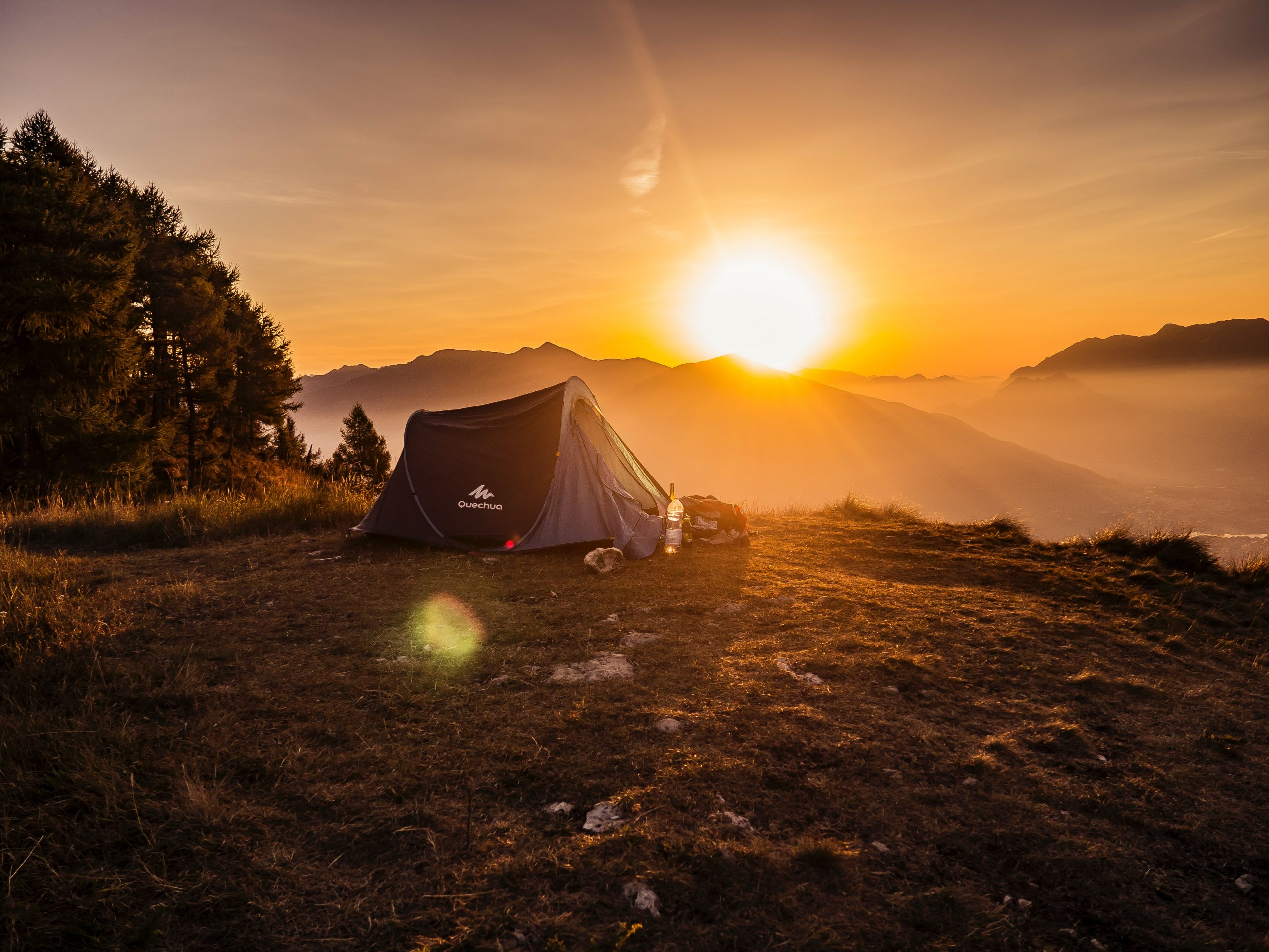 tent pitched on mountaintop campsite at sunset