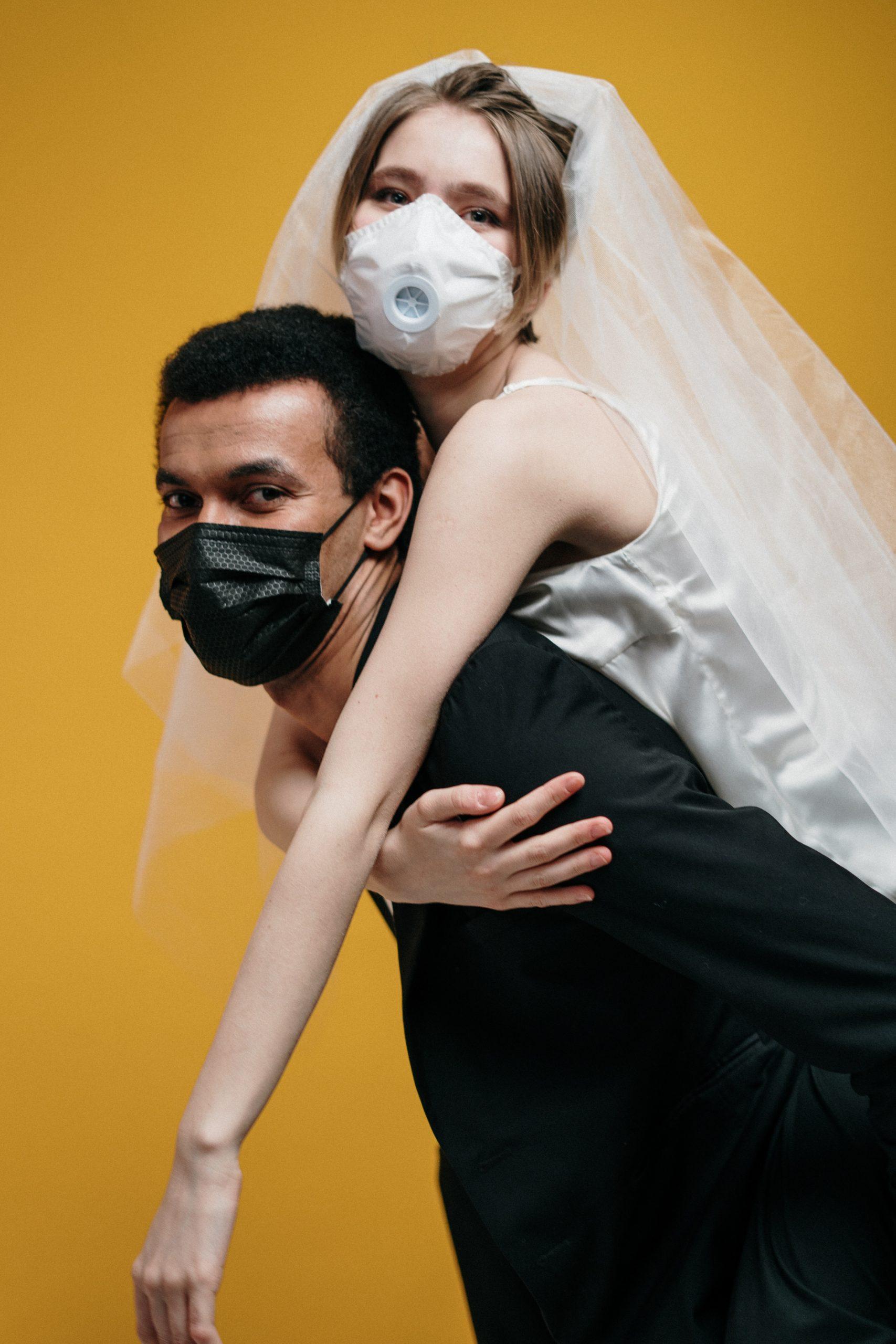 Bride and groom wearing masks; groom giving bride piggy back ride.