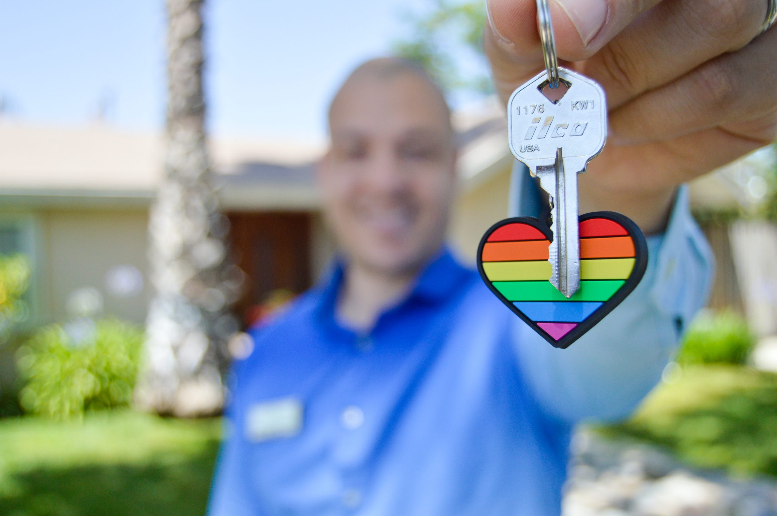 man holding up keys with rainbow keychain heart attached