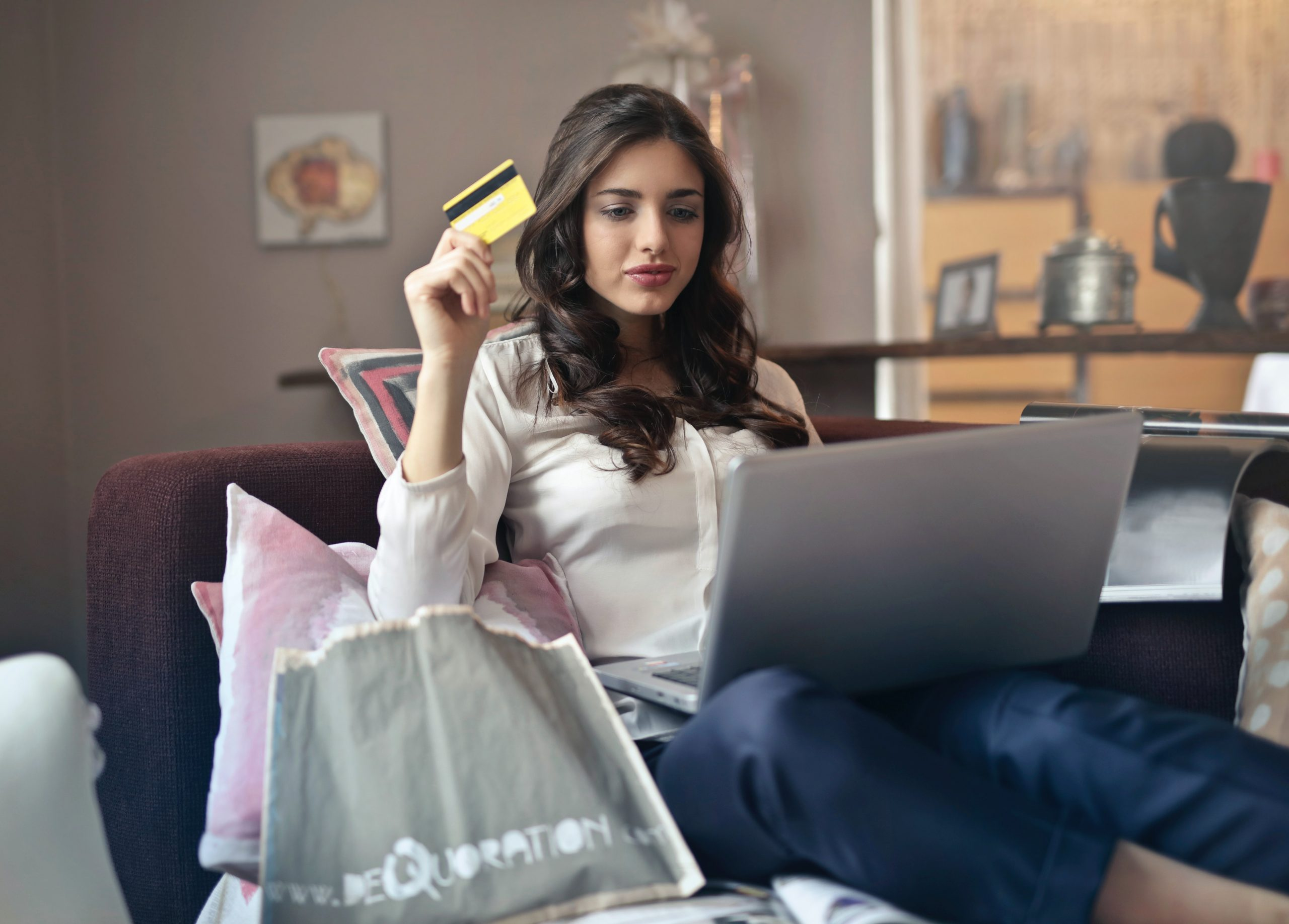woman shopping on computer holding up gift card