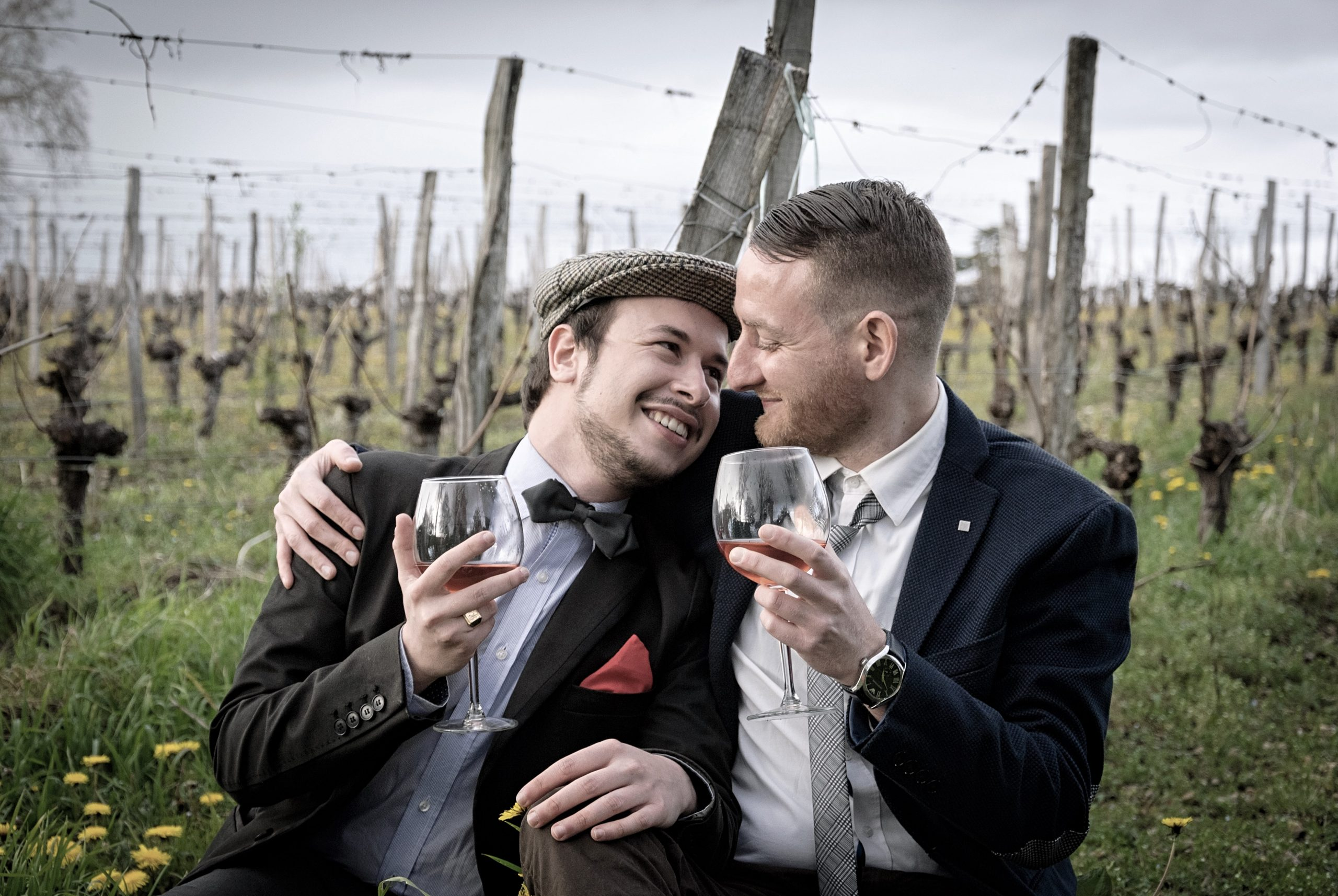 couple cuddling and drinking wine in formal wear