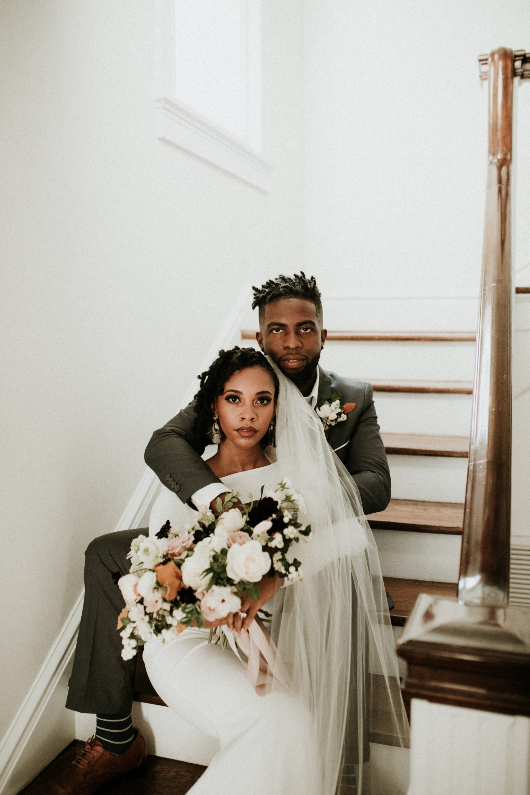 Bride and groom sitting on staircase.