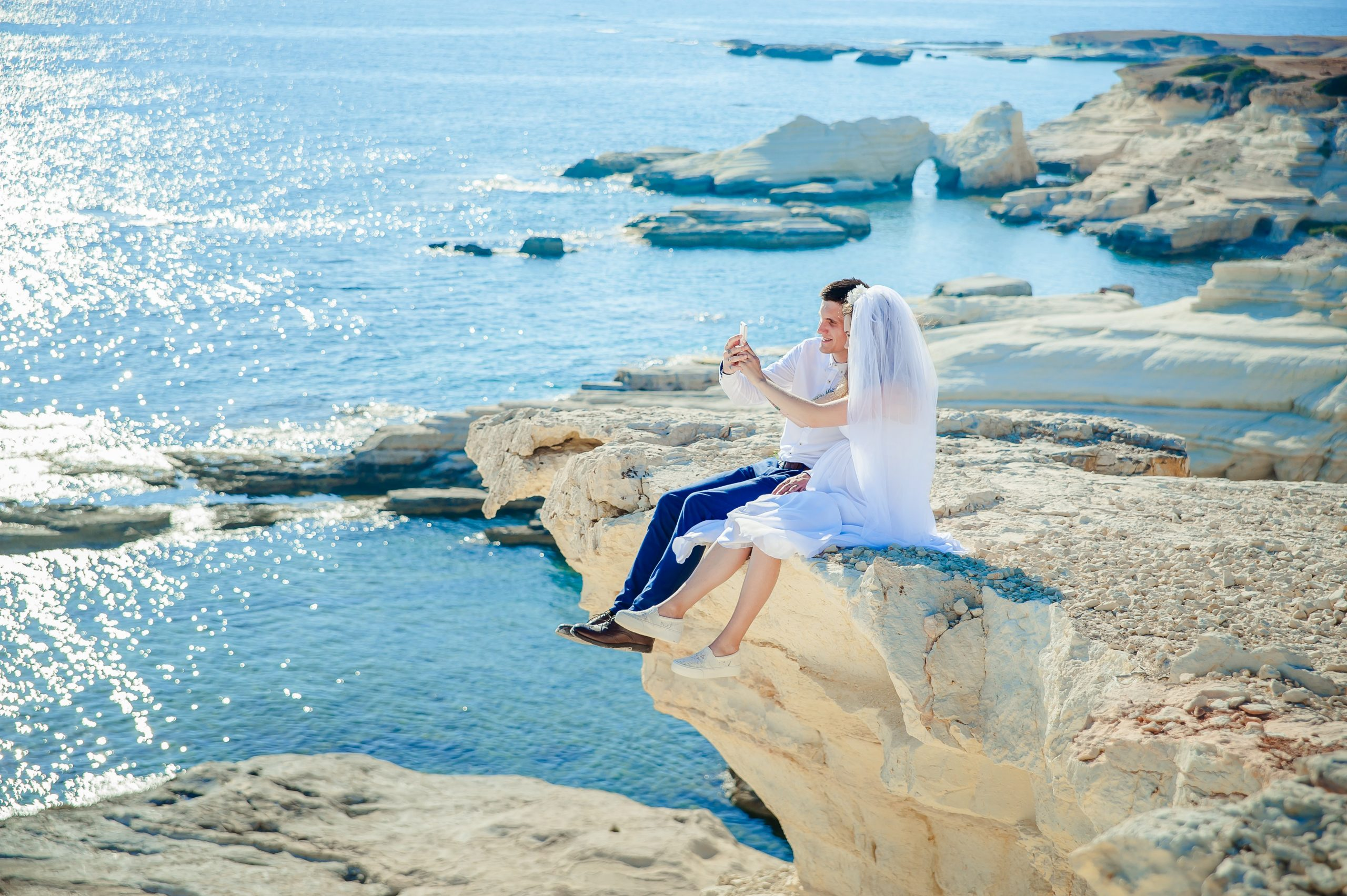 couple in weddingwear sitting on cliff above tropical water