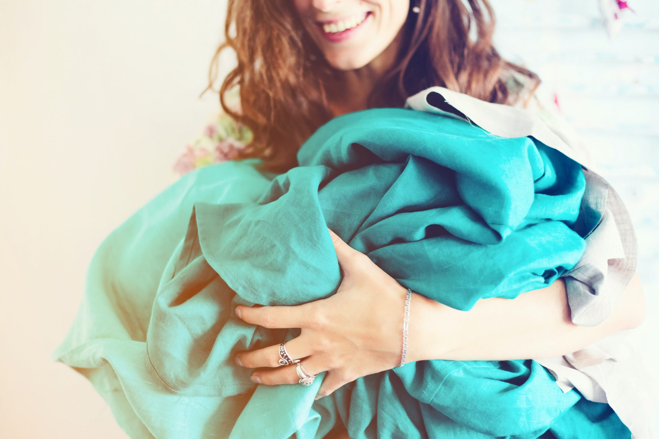 woman holding crumpled up sheets and blankets