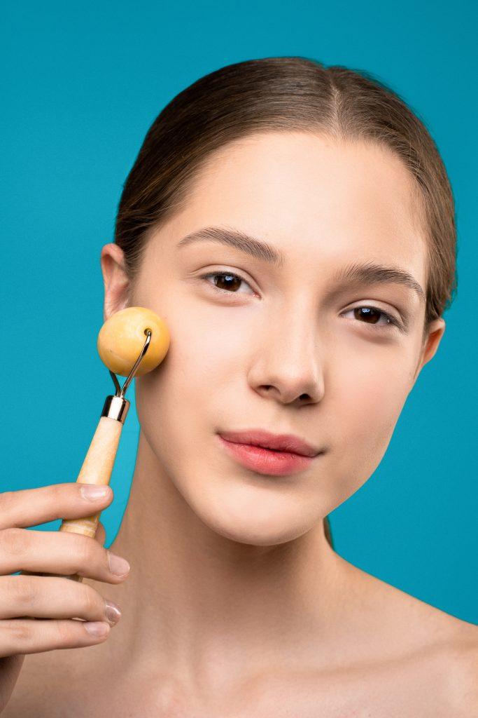 Woman using a face roller. -- DIY facial