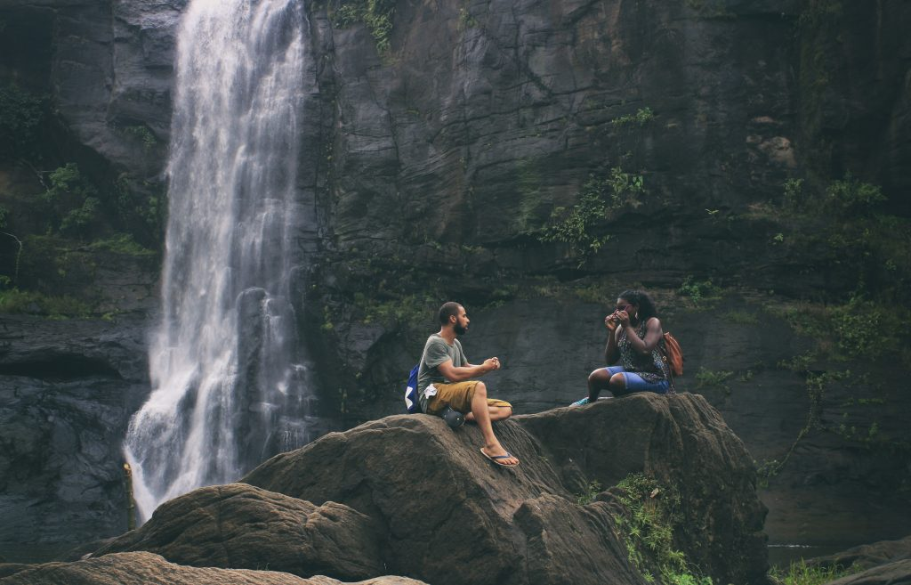 A couple sitting on a rock overlooking a waterfall