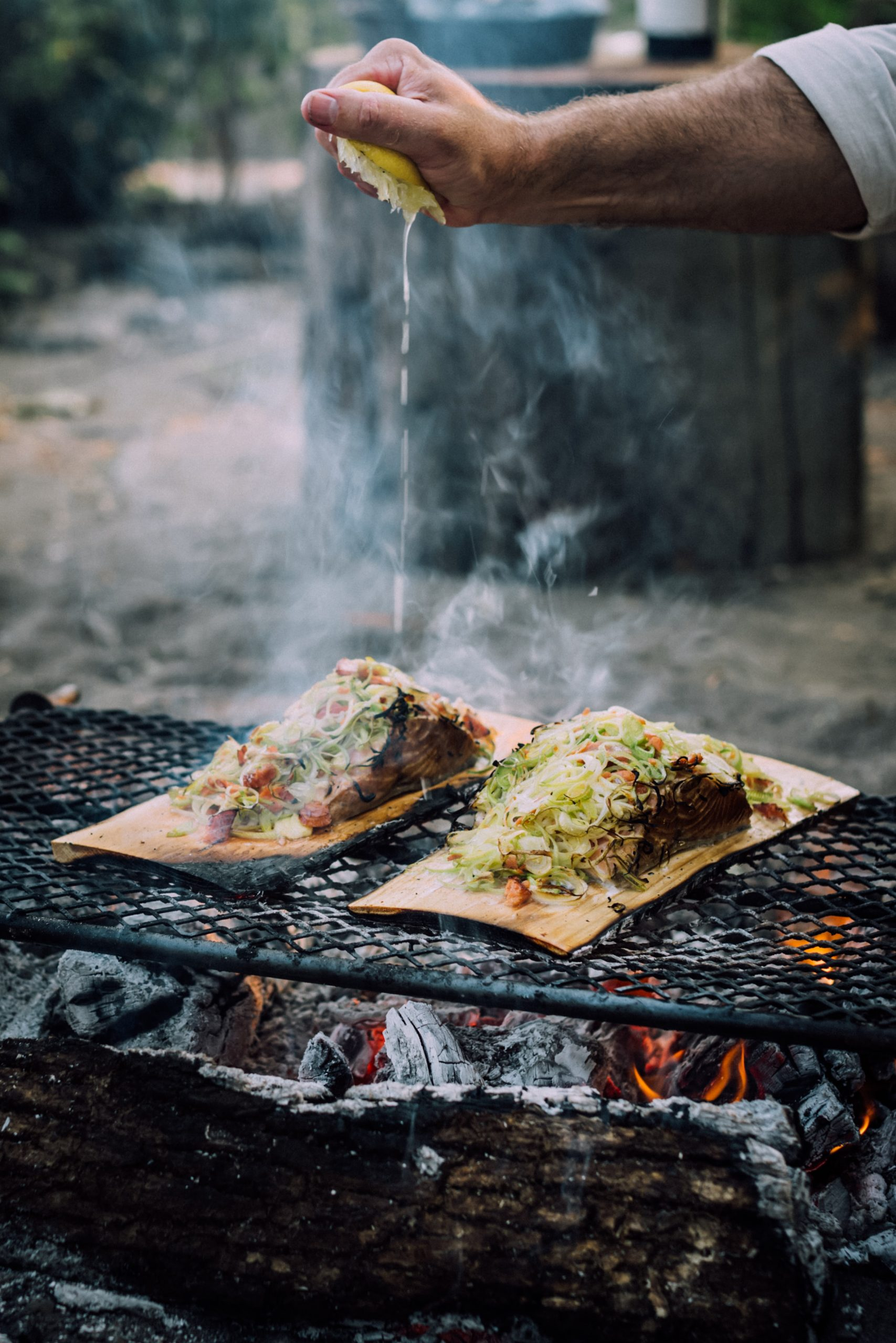 Cedar plank salmon and vegetables cooked over an open fire.