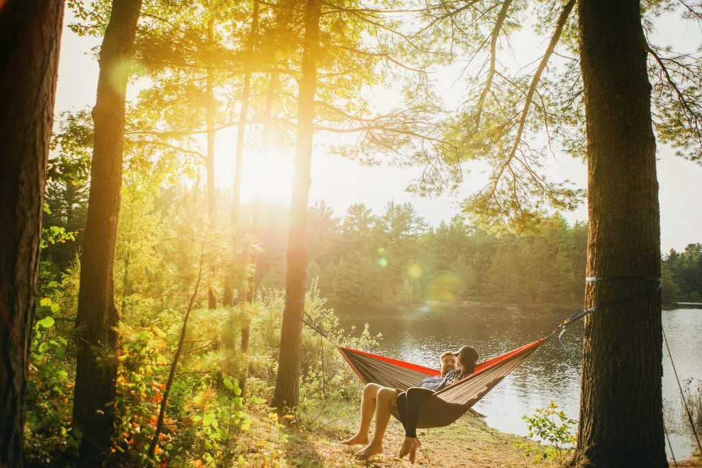 A couple in a hammock overlooking a lake