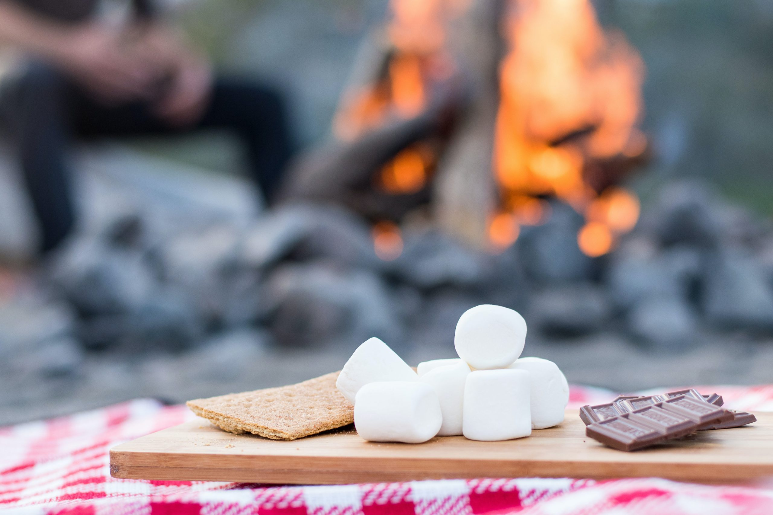 Smores ingrediants on a cutting baord by a fire pit