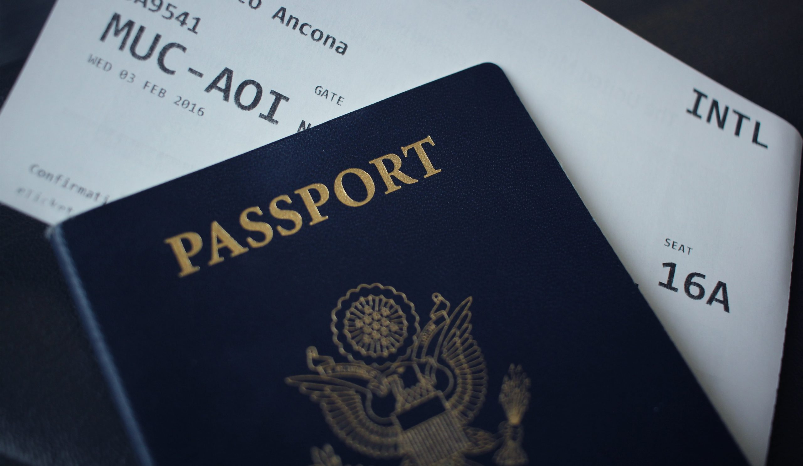 United States passport on top of boarding pass for plane