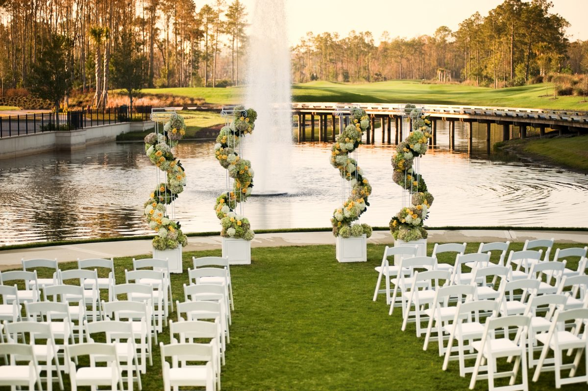 wedding chairs set up in front of pond with fountain and golf course in background