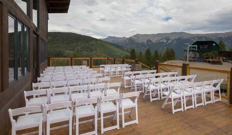 wedding ceremony chairs set up on outdoor patio overlooking mountain range