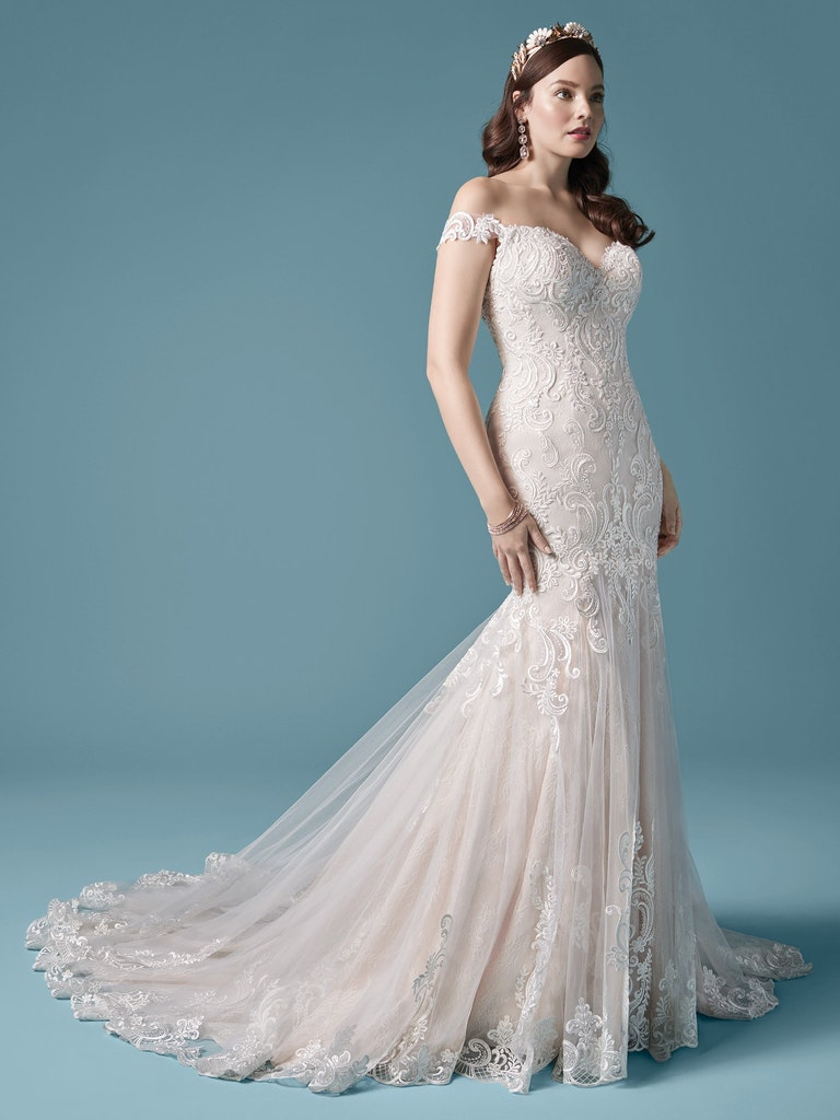 woman in cold-shoulder wedding dress with mermaid skirt and lace detailing