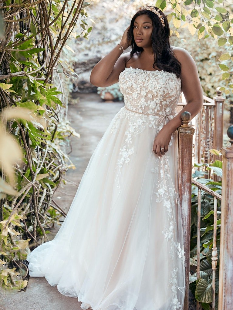 woman in garden wearing strapless wedding dress with cascading lace motifs