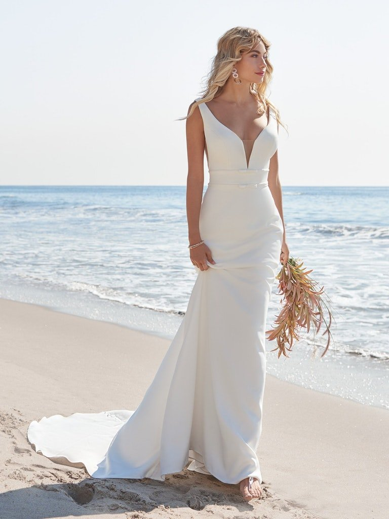 woman on beach in simple white sheath wedding dress with long train