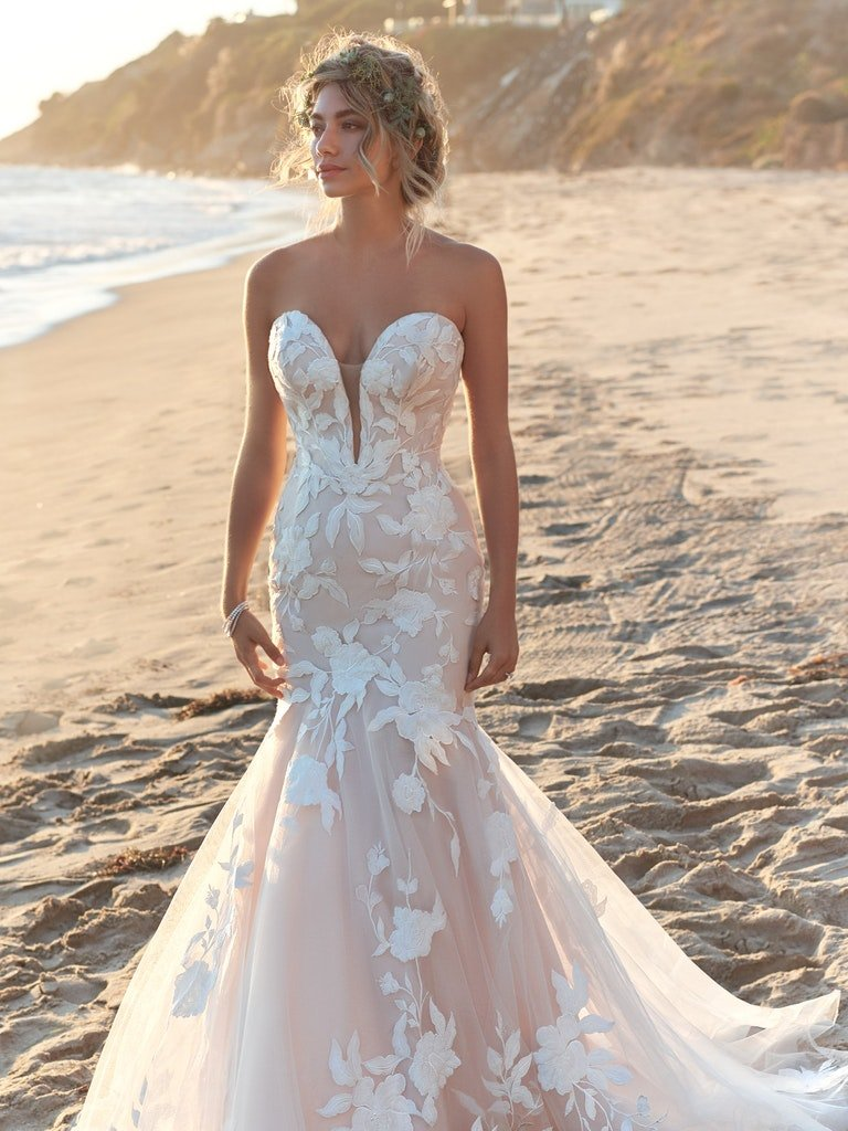 woman in beach in mermaid style wedding dress with large white floral lace detailing
