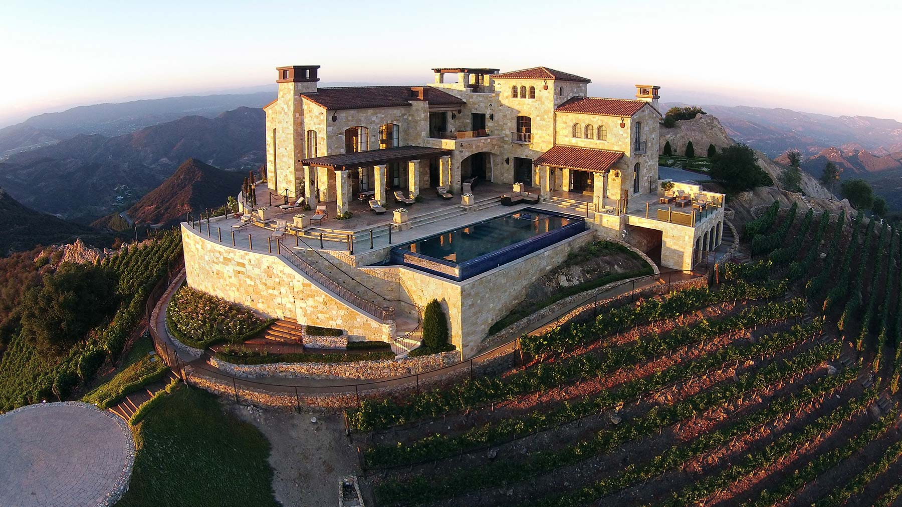 tuscan-style villa on top of mountain surrounded by vineyards