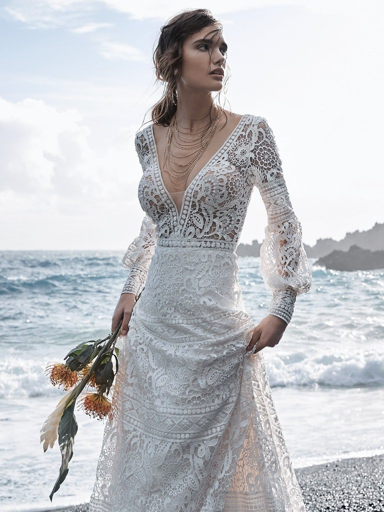 woman in full lace wedding dress with lace illusion bishop sleeves on a beach in front of the ocean