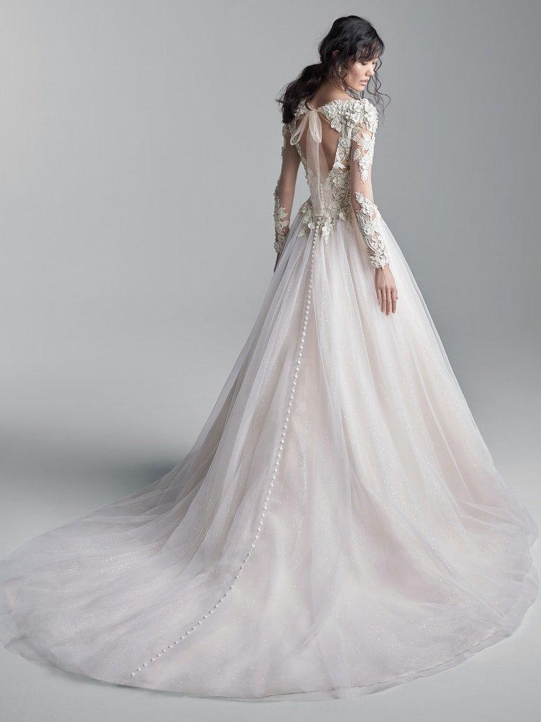 woman with her back to camera in layered tulle wedding dress with keyhole back and lace bodice and sleeves