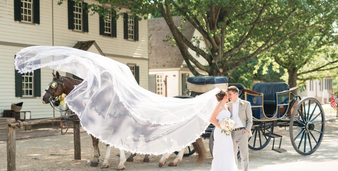bride with long veil and groom standing in front of horsedrawn carriage in Colonial Williamsburg