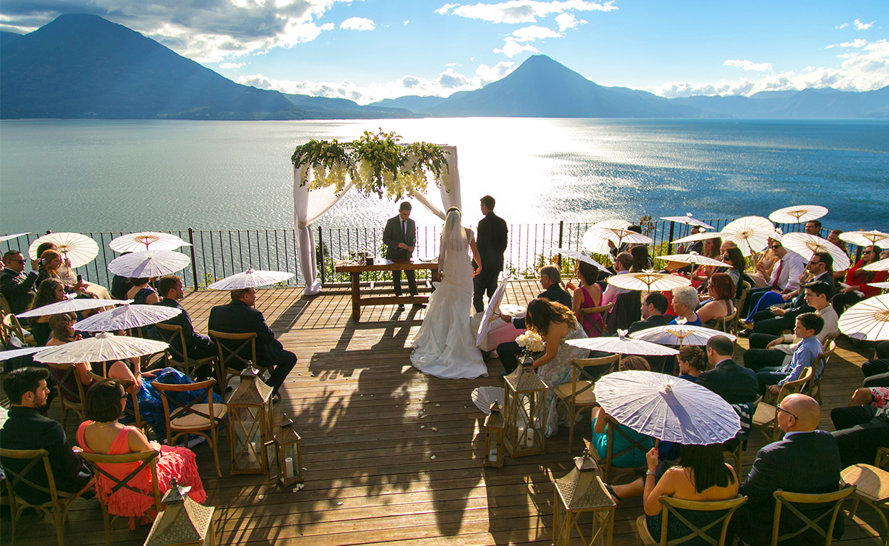 wedding ceremony on the banks of Lake Atitlán under a decorated flower arbor