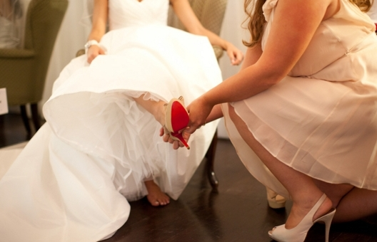 A bridesmaid helping a bride put on her shoe
