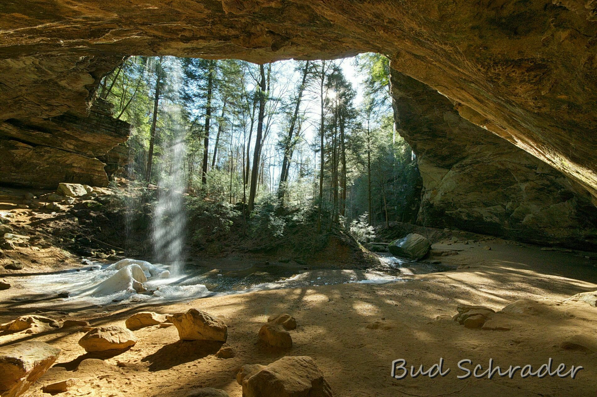 photo from inside of cave looking at curve of cave walls and sunlight streaming in