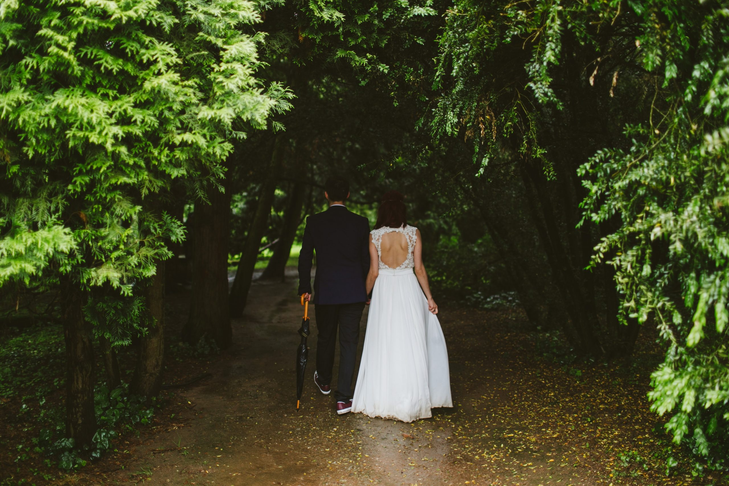 A bride and groom holding hands in a forest