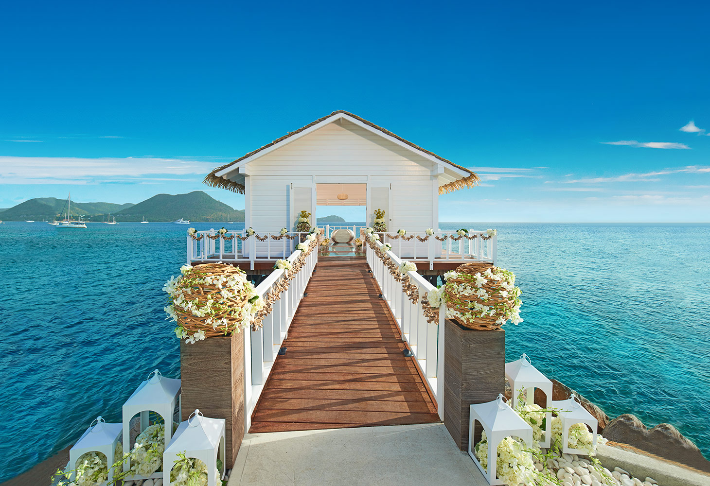 overwater wedding chapel with aisle decorated with flowers over blue ocean water