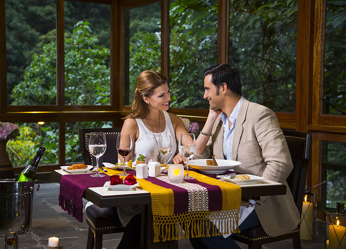 couple looking at each other over a meal of traditional Andean cuisine with forest in background