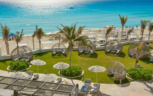 overlooking the beach and ocena with individual cabanas and palm trees on green lawn