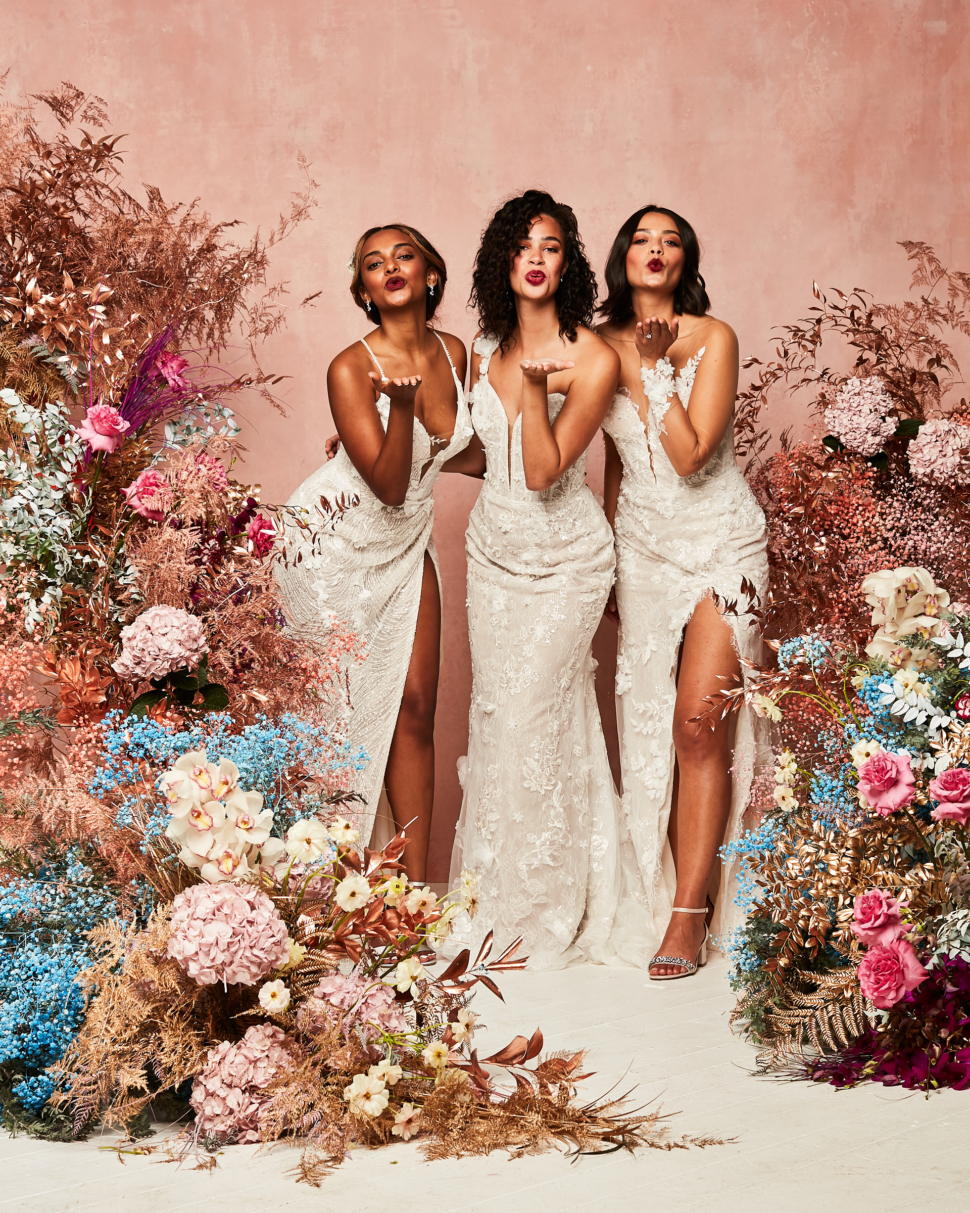 Three women modeling white David's Bridal spring 2021 collection dresses gowns and blowing kisses at the camera